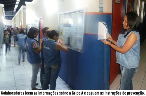 Colaboradores leem as informações sobre a Gripe A
